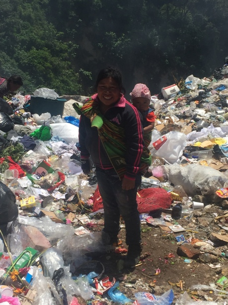 A women working at the dump with a 9 month child on her back.
